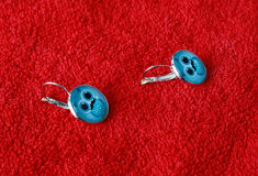 Pair of blue earrings on red background Royalty Free Stock Image