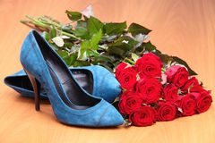 Pair of blue female shoes and bunch of red roses Royalty Free Stock Photos
