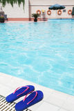 Pair of blue flip flops by the pool side Royalty Free Stock Photography