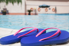 Pair of blue flip flops by the pool side Royalty Free Stock Images