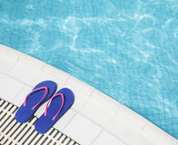 Pair of blue flip flops by the pool side Stock Photos