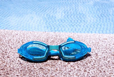 Pair of blue goggles by the pool Stock Image