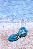 Pair of blue goggles by the pool Royalty Free Stock Image