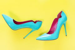 Pair of Blue high heels glassy shoes on yellow background, top view.  royalty free stock photos