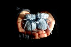 Pair of Blue Knitted Baby Booties in the Heart Shaped Palms of a Stock Image