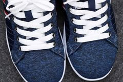 Pair of blue sneakers. Closeup of white shoelaces stock photo