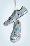 Pair of blue sneakers hangs on the laces Royalty Free Stock Image