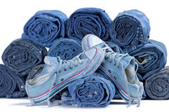 Pair of blue sneakers and stack of rolled colored jeans stock photos