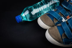 Pair of blue sneakers and water Stock Images