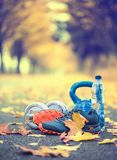Pair of blue sport shoes water and  dumbbells laid on a path in a tree autumn alley with maple leaves -  accessories for run exerc. Ise or workout activity Stock Photos