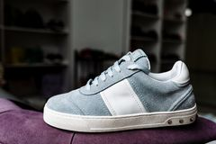 A pair of blue suede sneakers on a white sole with white accents on a background of shop royalty free stock image