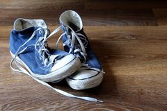 Pair of blue and white sneakers trainers boots on wooden background with space for text.  Royalty Free Stock Images