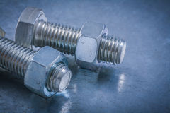 Pair of bolts and screw-nuts on metallic surface construction co Stock Image