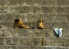 Pair of boots on concrete steps. With socks and laces seperate stock photography