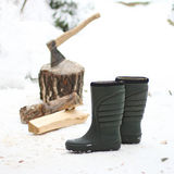 Pair of boots, firewood and axe in chump in the background. Winter Royalty Free Stock Images
