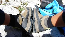 Pair of boots after a long walk. Pair of boots and blue backpack full of provisions stock image