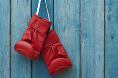 Pair of boxing gloves hanging in a rustic wooden wall Royalty Free Stock Image