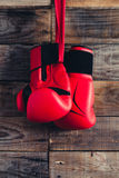 Pair of boxing gloves hanging in a rustic wooden wall. Retro style. Stock Photo