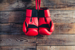 Pair of boxing gloves hanging in a rustic wooden wall. Vintage Royalty Free Stock Photography