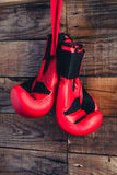 Pair of boxing gloves hanging in a rustic wooden wall. Vintage feel. Stock Photos