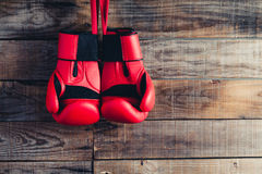 Pair of boxing gloves hanging in a rustic wooden wall. Vintage feel. Royalty Free Stock Image