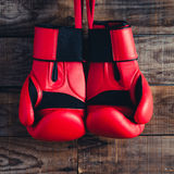 Pair of boxing gloves hanging in a rustic wooden wall. Vintage feel. Royalty Free Stock Photos