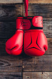 Pair of boxing gloves hanging in a rustic wooden wall. Vintage tone. Stock Photos