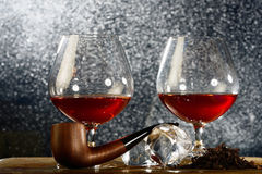 Pair of brandy snifters with smoking pipe Stock Photography