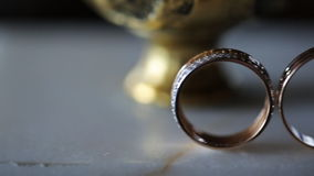 Pair of bridal rings stands on marmoreal table in room. Their golden surface is covered with shining brilliants that sparle under light of sun which penetrates stock footage