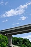 Pair of bridges crossing forest on sky. Pair of large concrete highway bridges crossing forest against partly cloudy sky Stock Photography