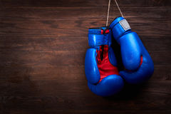A pair of bright blue and red boxing gloves hangs against wooden background. Stock Photography