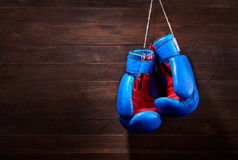 A pair of bright blue and red boxing gloves hangs against wooden background. Stock Photo