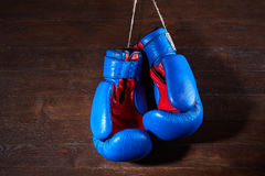 A pair of bright blue and red boxing gloves hangs against wooden background. Royalty Free Stock Photos