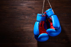 A pair of bright blue and red boxing gloves hangs against wooden background. Royalty Free Stock Photography