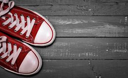 A pair of bright red textile sneakers. On a blue wooden background of boards, top view, vintage toning Royalty Free Stock Photography