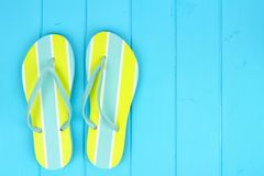 Pair of bright summer flip-flops against blue wood stock photography