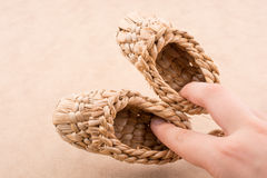 Pair of brown color straw shoes in hand on a brown background. Pair of brown color straw shoes hand on a brown background stock photos