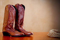 A pair of brown cowboy boots and a coil of rope. A horizontal image of a pair of brown cowboy boots and a coil of rope on a wooded surface with an old textured stock photos