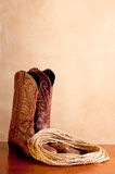 A pair of brown cowboy boots and rope Stock Image