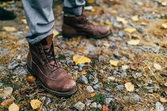 A pair of brown hiking boot in autumn forest. Soft focus on boot. Artwork stock photography