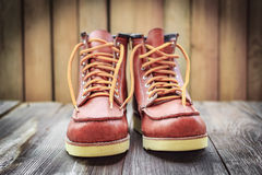 A pair of brown leather boots with laces placed on wooden floor Royalty Free Stock Photos