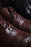 Pair of brown leather classic Brogue shoes on shelf with other shoes Royalty Free Stock Images