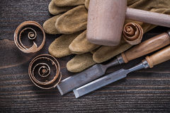 Pair of brown leather gloves firmer chisels wooden hammer and sh Stock Photos