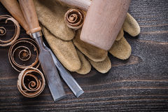 Pair of brown leather gloves firmer chisels wooden mallet and cu Royalty Free Stock Images