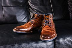 Brown Leather shoes displayed on black leather sofa. A pair of brown men`s leather shoes on black leather sofa Stock Photo