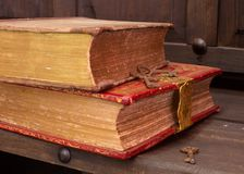 A pair of brown and red antique books on a wooden shelf with some old rusty skeleton keys. A pair of brown and red antique books with fancy trim on a wooden royalty free stock photo