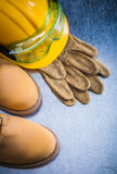Pair of brown safety lace shoes leather gloves hard hat and work Stock Photos