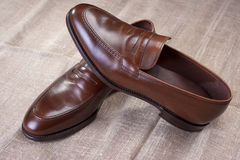 Pair of Brown Stylish Leather Penny Loafer Shoes Placed On Mesh Surface. Royalty Free Stock Photo