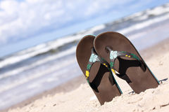 Pair of brown thongs. Tilted picture of pair of thongs put in sand on the summer beach Stock Photos