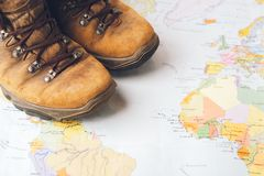 A pair of brown, worn suits against a geographical map. Selective focus. Concept of travel and adventure. Horizontal frame stock photos